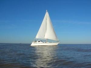 Velero blanco en un mar tranquilo y con cielo despejado